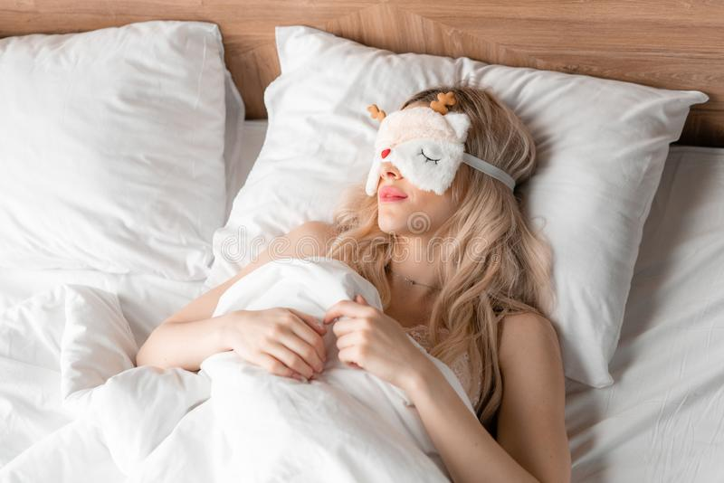 Jonge vrouwenslaap op comfortabel bed in een masker voor slaap Blinddoek op oog Ochtend in hotelruimte Wit hoofdkussen en royalty-vrije stock foto's