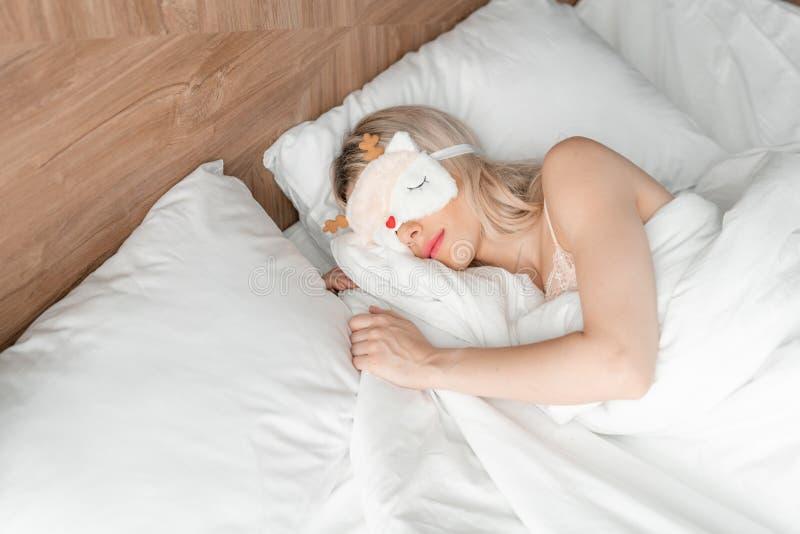 Jonge vrouwenslaap op comfortabel bed in een masker voor slaap Blinddoek op oog Ochtend in hotelruimte Wit hoofdkussen en stock afbeeldingen