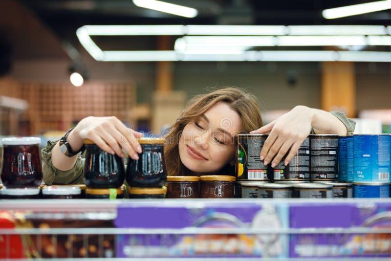 Jonge vrouwenslaap op kruidenierswinkels op een supermarktdoorgang royalty-vrije stock foto's