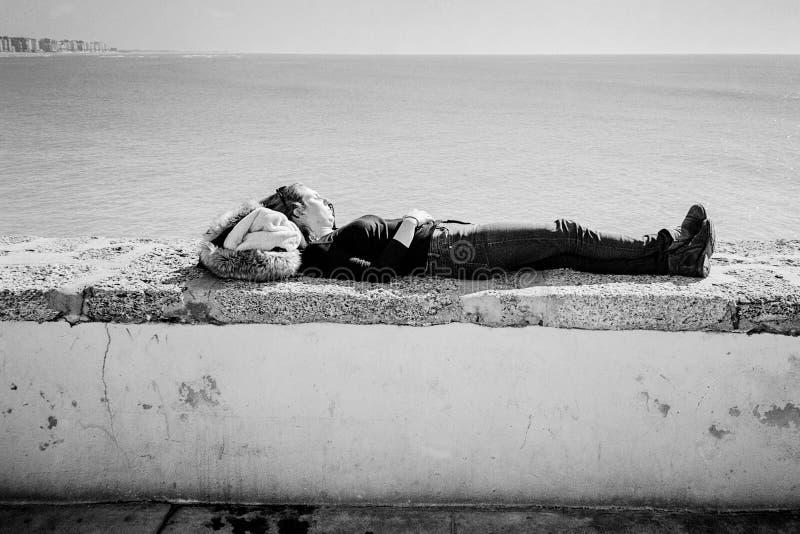 Jonge Vrouwenslaap op Zeedijk in Cadiz, Spanje stock afbeeldingen