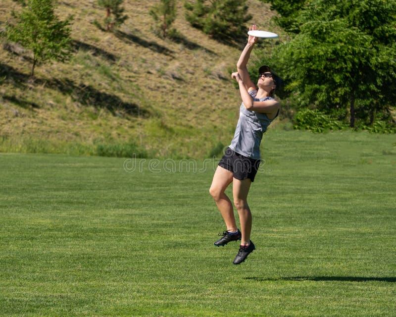 Jonge vrouwensprongen voor vliegende schijf stock afbeeldingen