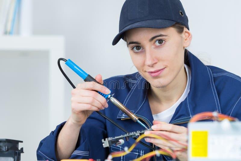 Jonge vrouwentechnicus die elektronikaapparaat herstellen royalty-vrije stock afbeeldingen
