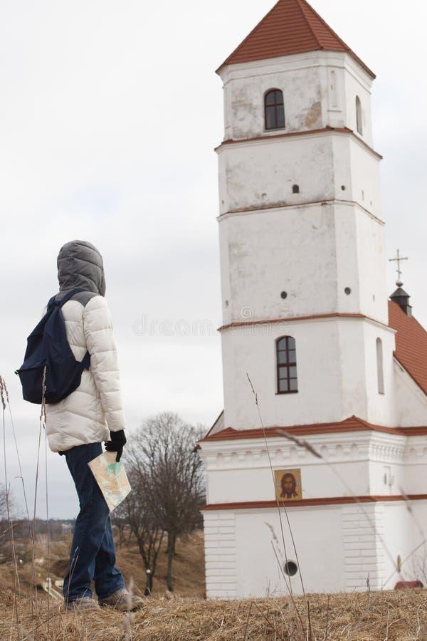 Jonge vrouwentoerist die de kaart op de achtergrond van het kasteel bekijken stock fotografie