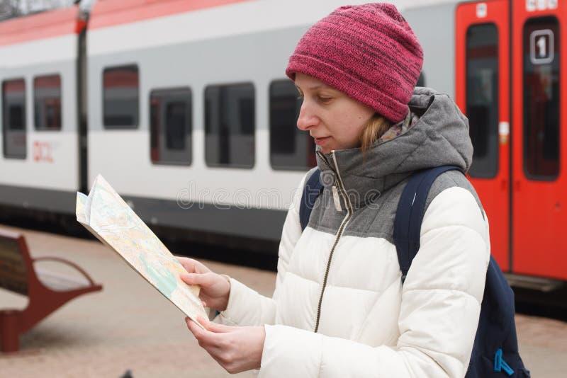 Jonge vrouwentoerist die de kaart op de achtergrond van de trein bekijken royalty-vrije stock afbeeldingen