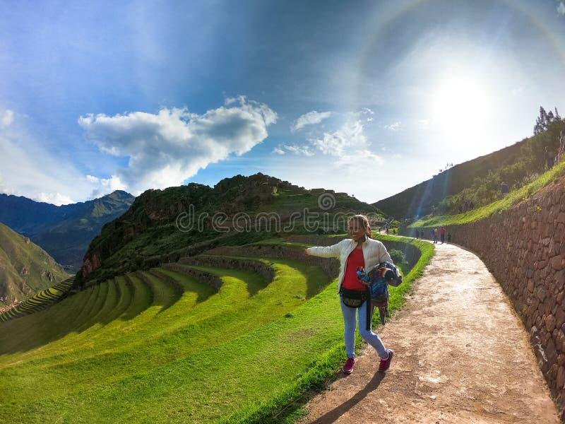 Jonge vrouwentoerist die de ru?nes van Pisac Inca in Peru bekijken royalty-vrije stock foto