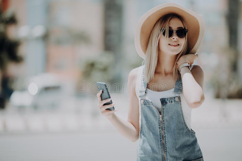 Jonge vrouwentoerist in hoed die gps navigatie op telefoon gebruiken online boekend De stijl van de de zomermanier Stadsreis Onde stock foto
