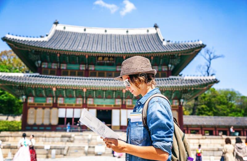 Jonge vrouwentoerist met kaart in hand op de achtergrond van Aziaat stock afbeeldingen