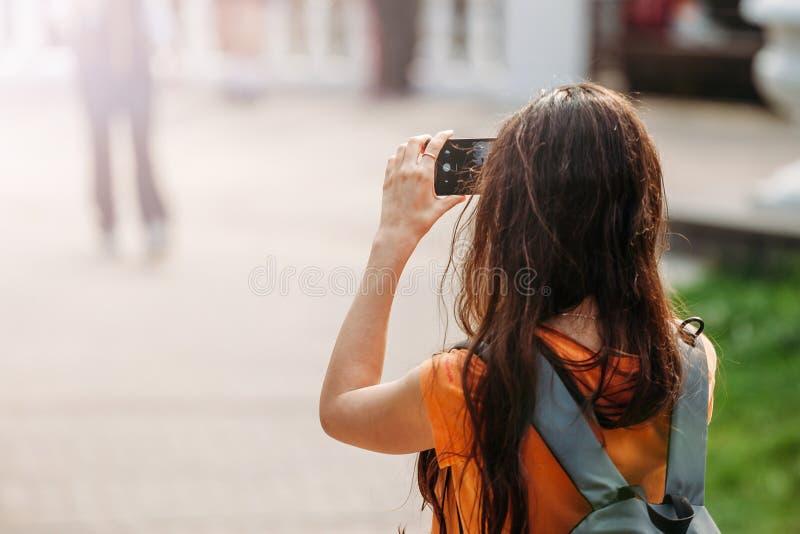 Jonge vrouwentoerist met rugzak die beelden op smartphone in openlucht nemen stock foto's