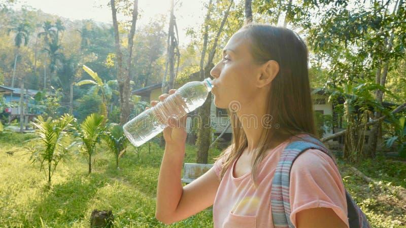 Jonge vrouwentribune op plattelandsweg in Aziatisch dorp en drinkwater royalty-vrije stock foto