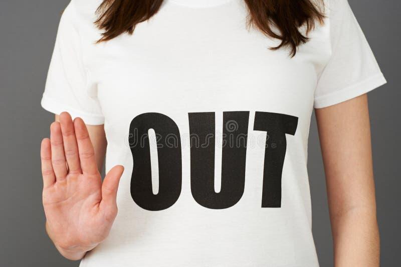 Jonge Vrouwenverdediger die die T-shirt dragen met UIT Slogan wordt gedrukt royalty-vrije stock foto