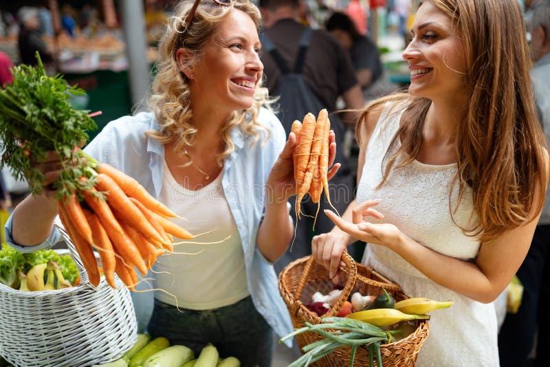 Jonge vrouwenvrienden die groenten en vruchten op de markt blaffen royalty-vrije stock fotografie
