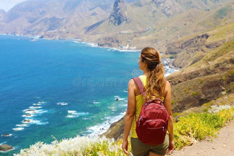 Jonge vrouwenwandelaar die bewonderend het Eilandlandschap van Tenerife in een gezond actief levensstijlconcept bevinden zich stock afbeeldingen