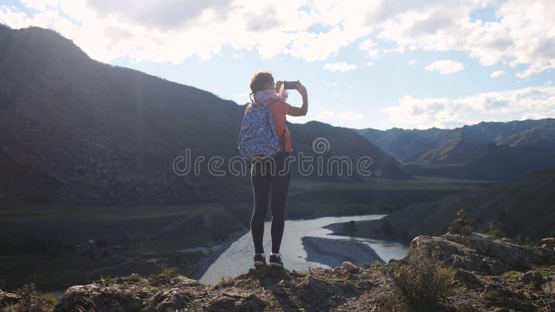 Jonge vrouwenwandelaar die foto met slimme telefoon nemen bij berg piekklip met de gevolgen van de zongloed royalty-vrije stock foto