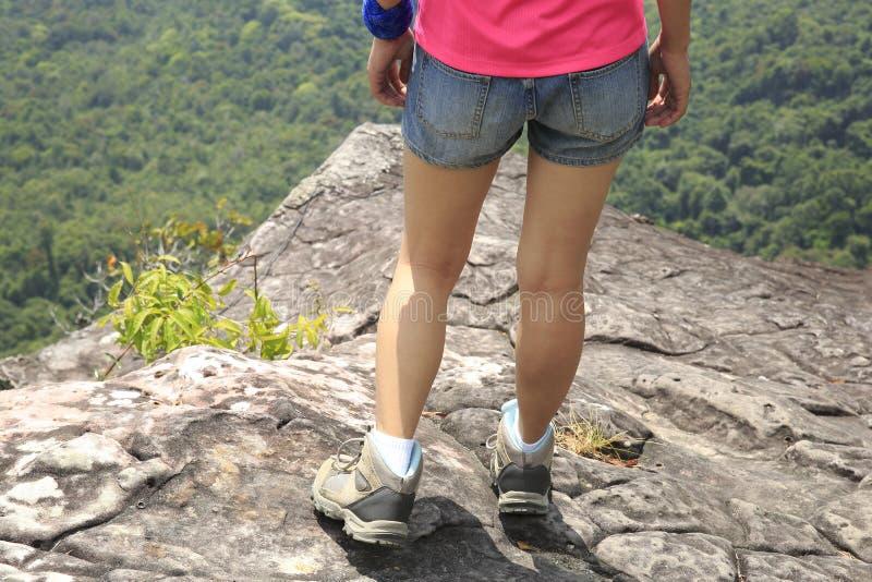 Jonge vrouwenwandelaar die zich op bergpiek bevinden royalty-vrije stock foto