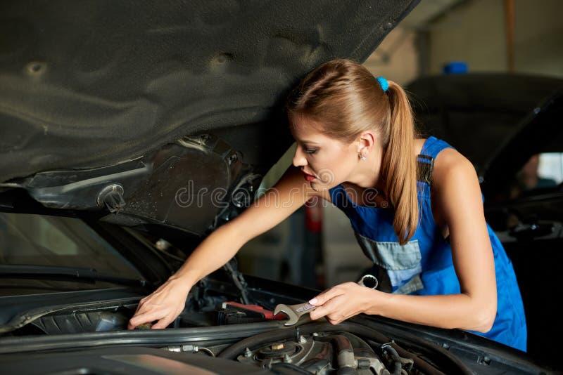 Jonge vrouwenwerktuigkundigen die of een auto herstellen inspecteren stock foto