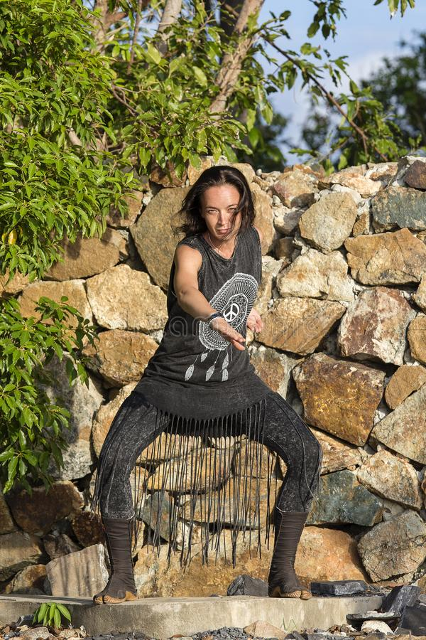 Jonge vrouwenyoga die shamanic dans op een aardachtergrond doen royalty-vrije stock afbeeldingen