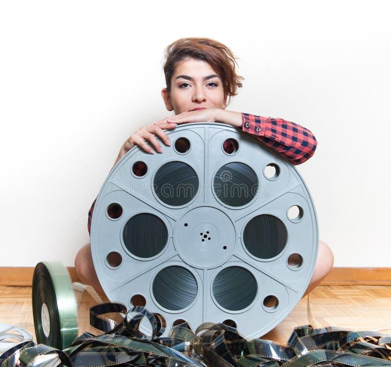 Jonge vrouwenzitting achter de grote spoel van de bioskoopfilm royalty-vrije stock fotografie