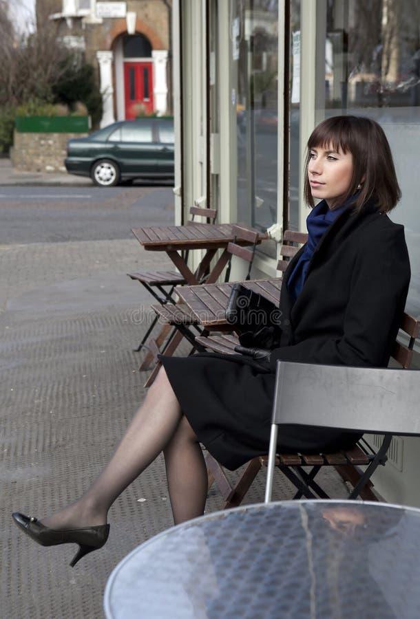 Jonge vrouwenzitting alleen in straatkoffie royalty-vrije stock fotografie