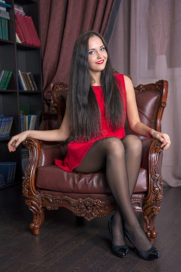 Jonge vrouwenzitting als leervoorzitter royalty-vrije stock fotografie