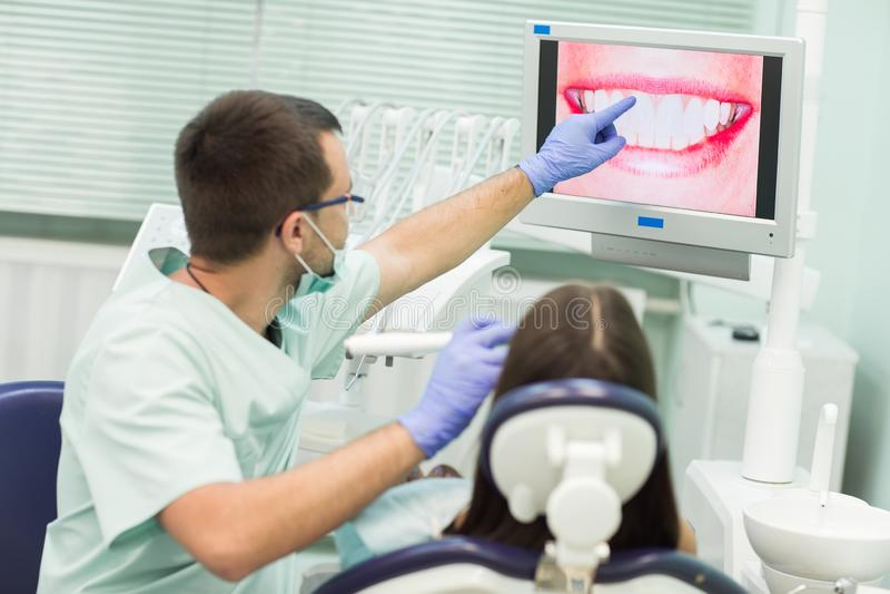 Jonge vrouwenzitting als voorzitter van de tandarts met geopende mond op het kantoor van de tandarts terwijl het hebben van onder royalty-vrije stock foto's