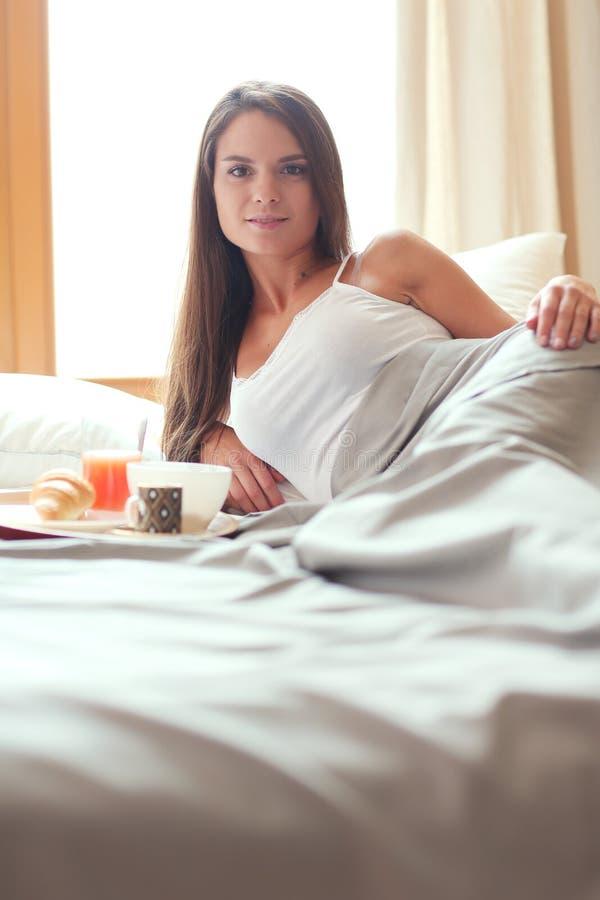 Download Jonge Vrouwenzitting In Bed Met Een Kop Van Melk Stock Foto - Afbeelding bestaande uit blootvoets, drinking: 107703174