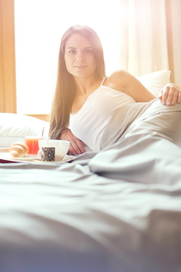 Download Jonge Vrouwenzitting In Bed Met Een Kop Van Melk Stock Afbeelding - Afbeelding bestaande uit ochtend, slaapkamer: 107704175