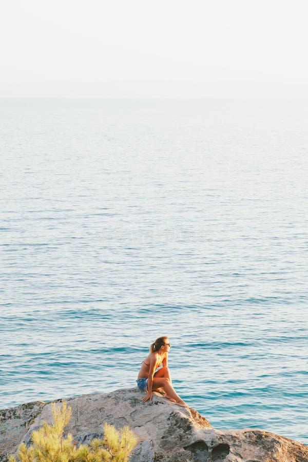 Jonge vrouwenzitting bij de rand van de klip stock foto