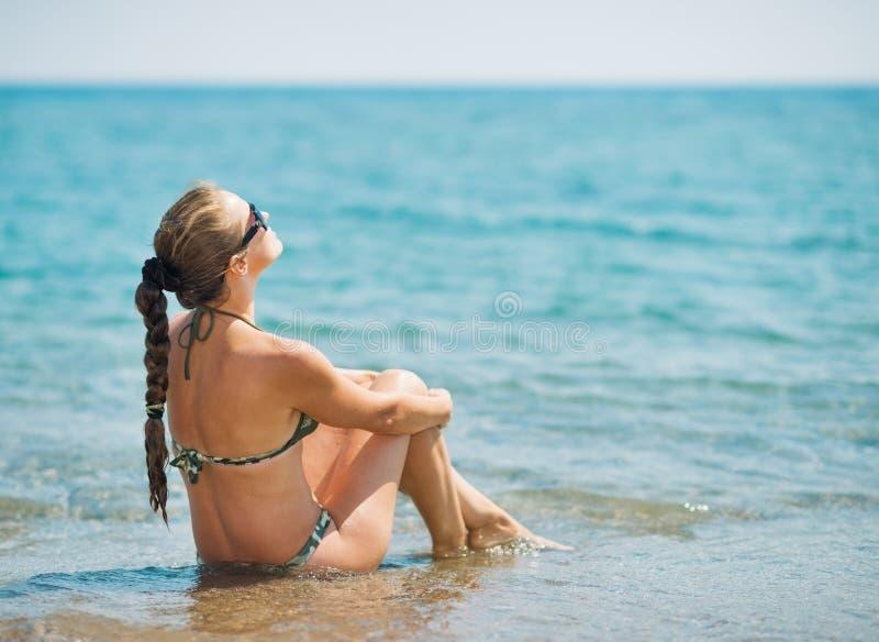 Jonge vrouwenzitting bij kust. stock foto's