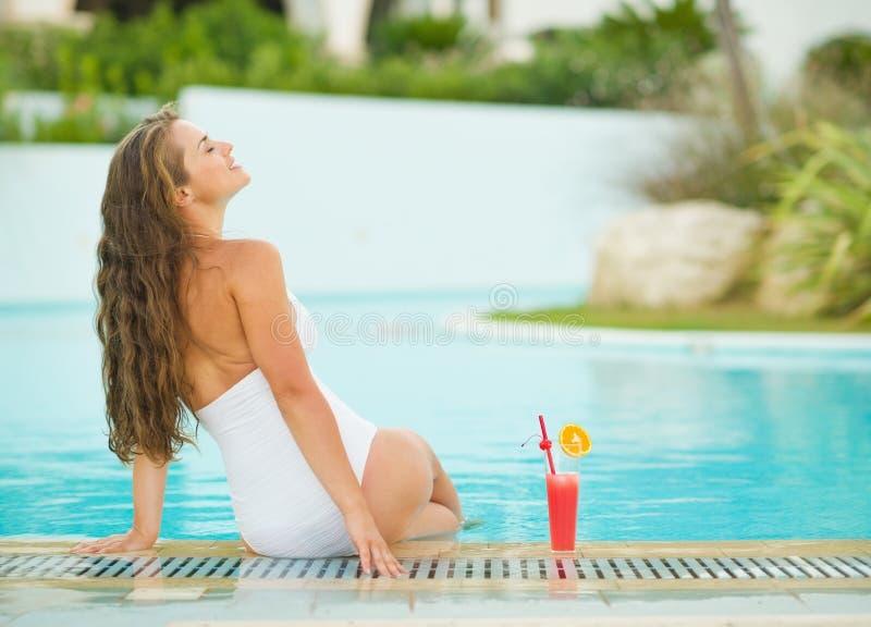 Jonge vrouwenzitting bij poolside met cocktail stock foto