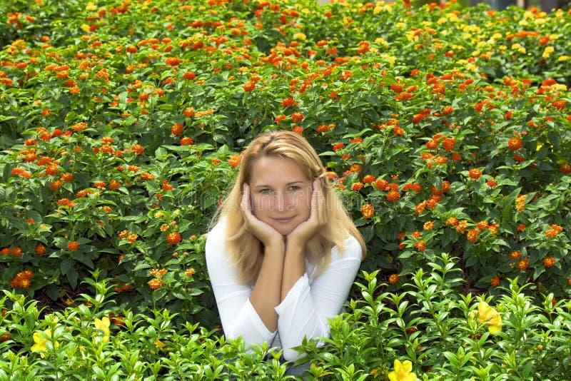 Jonge vrouwenzitting in bloemen royalty-vrije stock foto