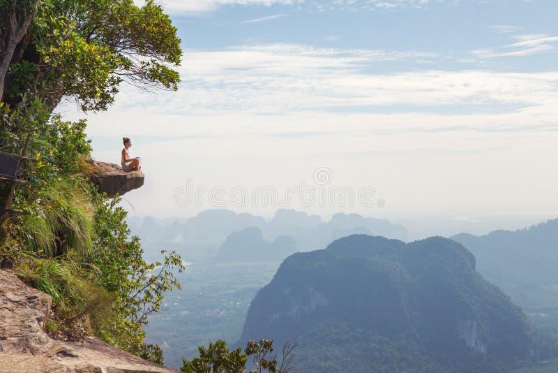 Jonge vrouwenzitting bovenop een berg en het ontspannen royalty-vrije stock fotografie