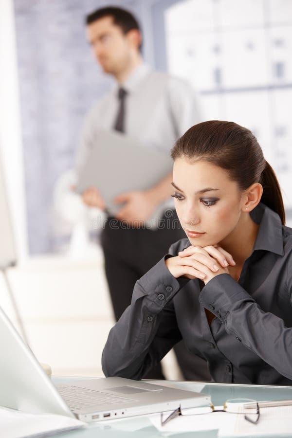 Jonge vrouwenzitting in bureau dat laptop met behulp van royalty-vrije stock afbeelding