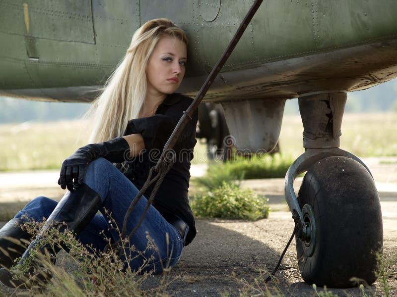 Jonge vrouwenzitting dichtbij vliegtuig stock foto's
