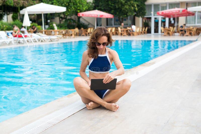 Jonge vrouwenzitting door de pool en het werken aan laptop Vrouwenwerkverslaafde die terwijl op vakantie, beschikbare ruimte werk royalty-vrije stock fotografie