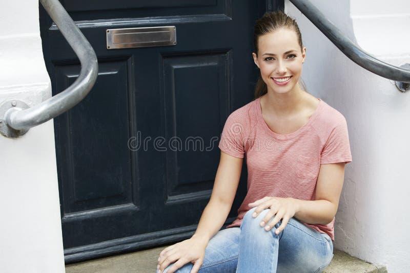 Jonge vrouwenzitting door voordeur, het glimlachen royalty-vrije stock afbeelding
