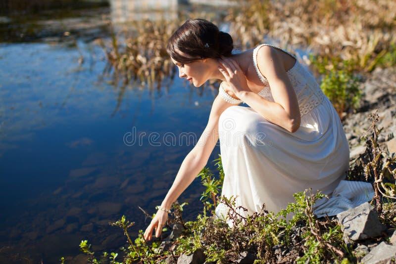 Jonge vrouwenzitting door water royalty-vrije stock fotografie