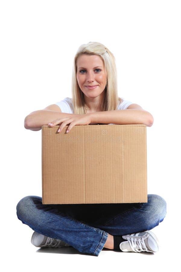 Jonge vrouwenzitting en holding een bewegende doos royalty-vrije stock afbeelding