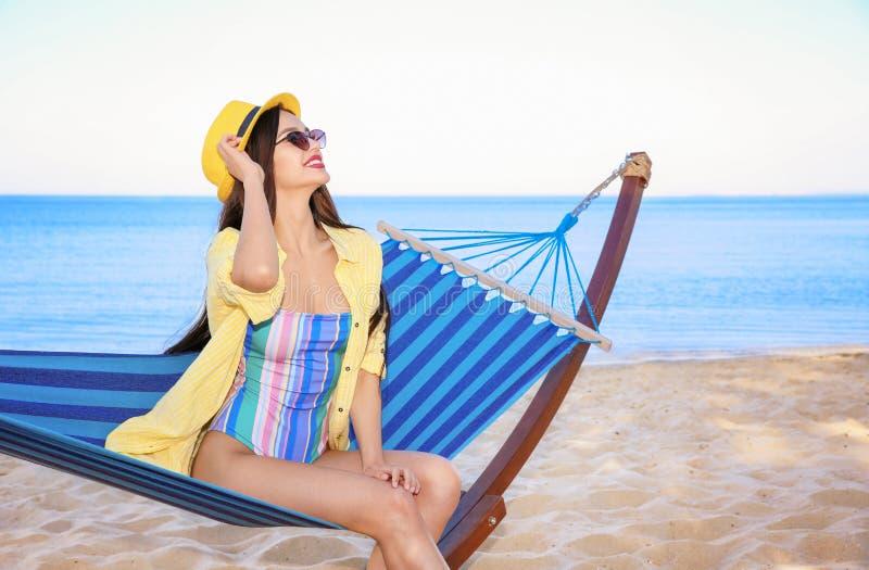 Jonge vrouwenzitting in hangmat bij kust royalty-vrije stock afbeeldingen