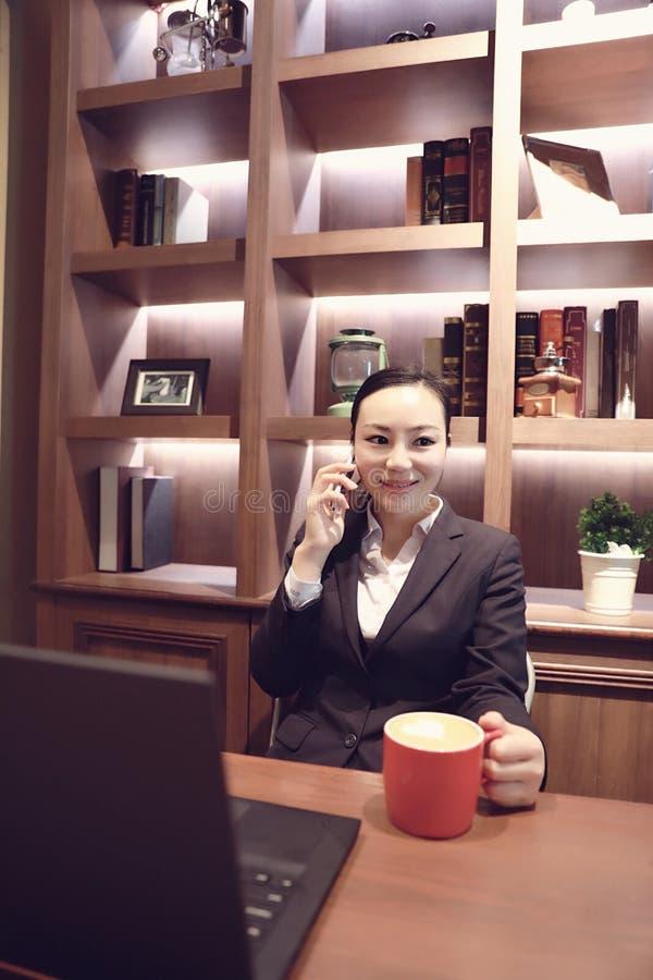 Jonge vrouwenzitting in koffiewinkel bij houten lijst, het drinken koffie en het gebruiken van smartphone Op lijst is laptop stock afbeelding