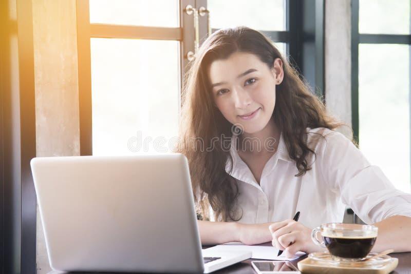 Jonge vrouwenzitting in koffiewinkel bij houten lijst, het drinken koffie en het gebruiken van smartphone Op lijst is laptop voor stock foto's