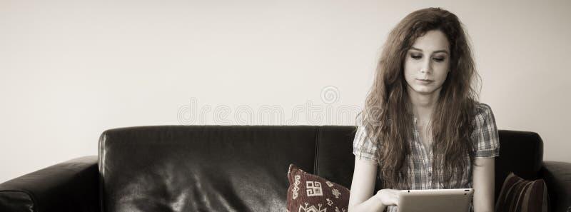 Jonge vrouwenzitting met een tablet in een laag stock fotografie