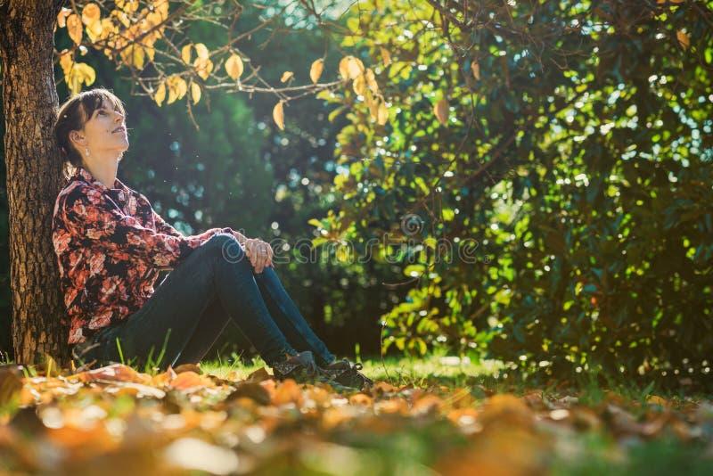 Jonge vrouwenzitting onder een de herfstboom royalty-vrije stock foto's