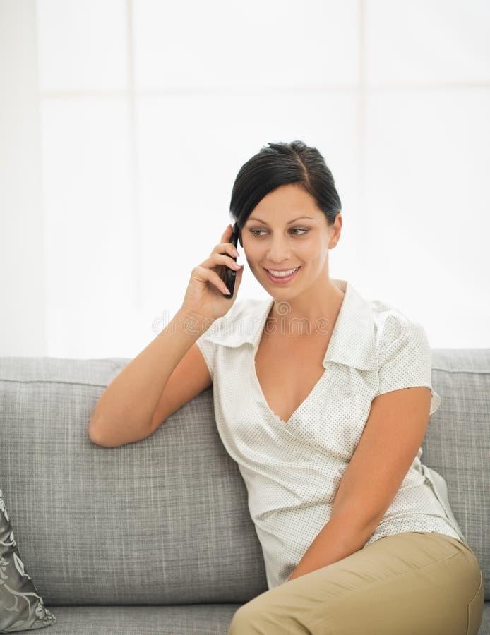 Jonge vrouwenzitting op bank en mobiel spreken stock afbeelding