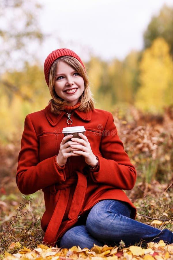 Jonge vrouwenzitting op dalende bladeren stock afbeeldingen