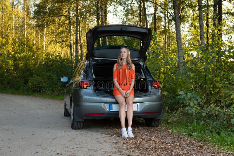 Jonge vrouwenzitting op de rand van de gebroken autolaars en het wachten voor hulp stock fotografie