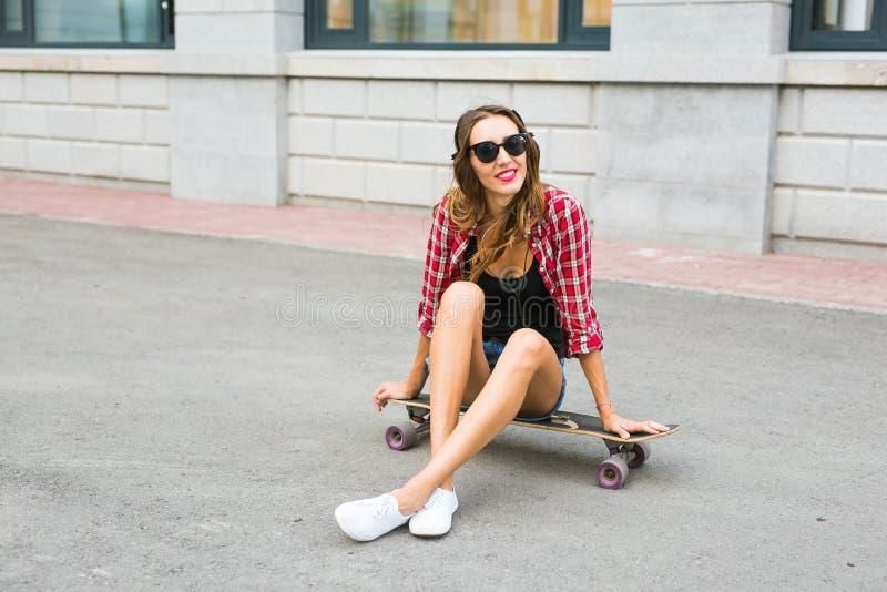 Jonge vrouwenzitting op de schaatser Glimlachende vrouw met skateboard in in openlucht stock afbeelding