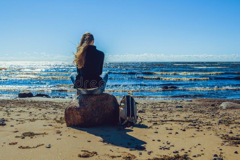 Jonge vrouwenzitting op de steen bij de kust stock foto's