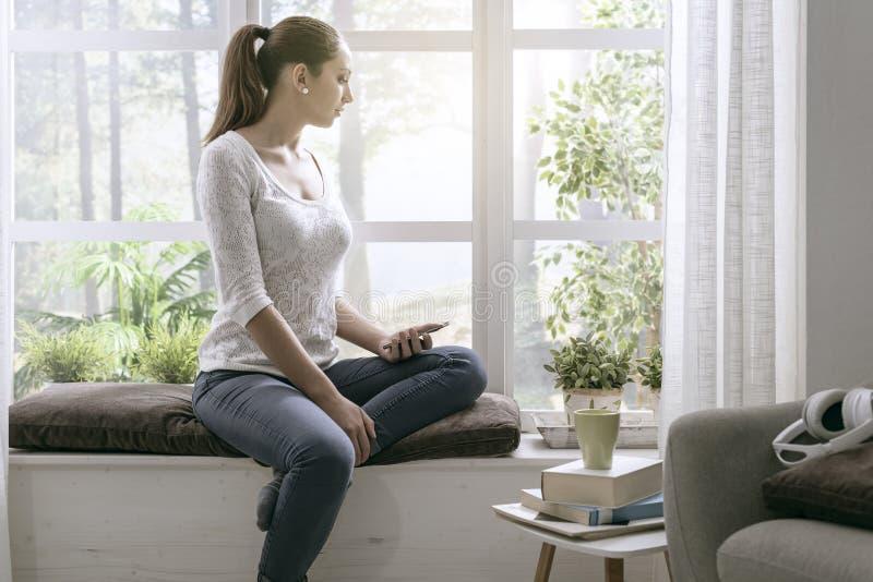 Jonge vrouwenzitting op de vensterbank en het gebruiken van haar telefoon royalty-vrije stock foto's
