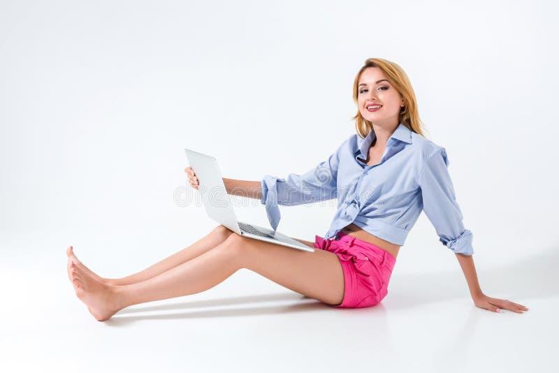 Jonge vrouwenzitting op de vloer en het gebruiken van laptop royalty-vrije stock fotografie