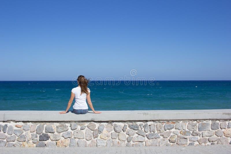 Jonge vrouwenzitting op dijk royalty-vrije stock afbeelding